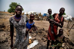 DABLUAL, SOUTH SUDAN - MARCH 23, 2017: (Left to right) Nyakuma Tap and her older sister Nyakuoth Kuol, hold their babies on the remnants of their former shelter in Dablual (Mayendit), South Sudan, on March 23, 2017. They explain an attack by armed men destroyed their house last October. Hundreds of people have recently fled Dablual, still under control of the opposition troops (SPLA-IO), due to the ongoing fighting and food crisis. Insecurity and lack of access have left some 100,000 people facing starvation in Leer and Mayendit counties, where famine was declared by the UN on 20 February, and a further one million are on the brink of famine. According to the UNOCHA, by the height of the lean season in July, it is expected that some 5.5 million people will be severely food insecure across the country. Since December 2013, about 3.4 million people have been displaced, including nearly 1.9 million people who have been internally displaced and about 1.5 million who have fled as refugees to neighbouring countries. (Photo by Albert Gonzalez Farran for The Washington Post via Getty Images)